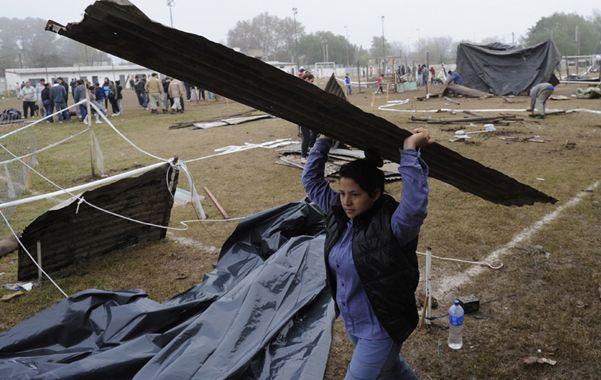 No va más.  Una mujer desmantela una de las precarias viviendas que se habían montado en la canchita de fútbol de 27 de Febrero al 4200.