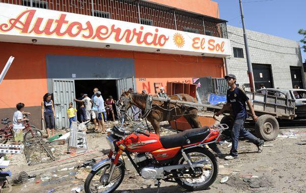 Triste Postal. Un grupo de vecinos ingresa por una de las puertas violentadas de un supermercado de la zona sur de la ciudad.