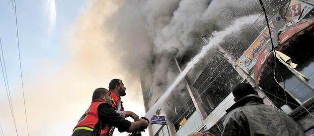 Bomberos palestinos combaten el incendio de un edificio de Hamas bombardeado por Israel.