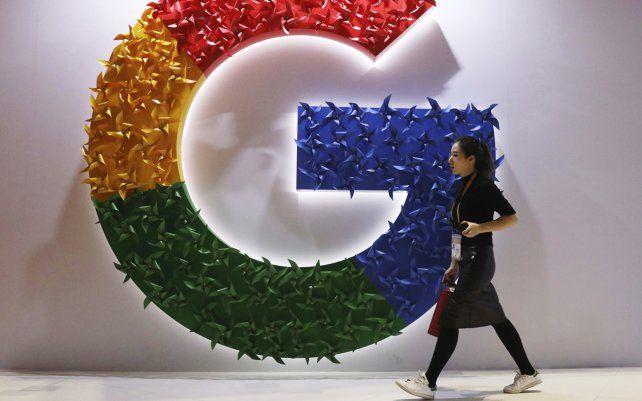 Una mujer pasa junto al logotipo de Google en la Exposición Internacional de Importaciones de China en Shanghai. El organismo de control anticompetitivo de Francia ha decidido multar a Google con 220 millones de euros por abusar de su posición dominante.