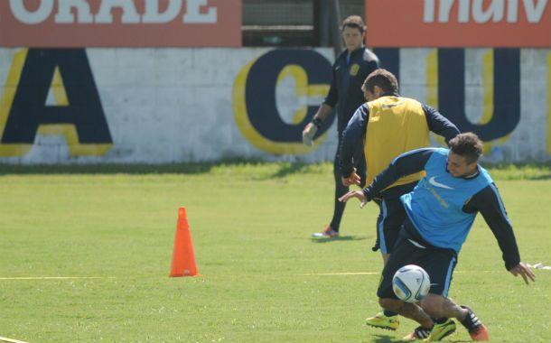 El defensor (pechera azul) quita una pelota en medio de un trabajo en espacios reducidos.