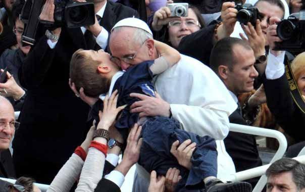 El Santo Padre. Jorge Bergoglio besó especialmente a un niño enfermo que le acercaron ayer en la plaza San Pedro.