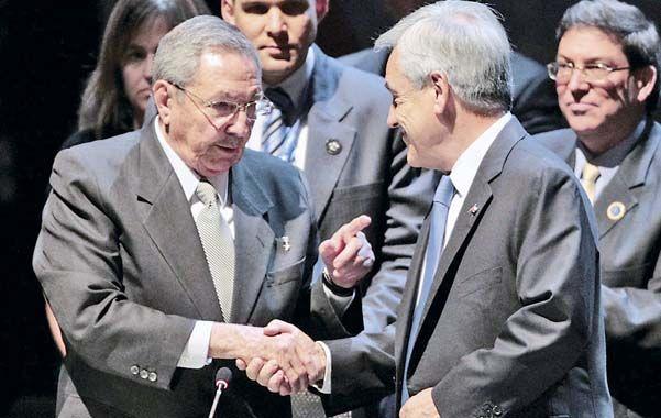 Traspaso. Raúl Castro y Piñera se saludan. El chileno le recordó al cubano que la Celac debe defender la democracia.