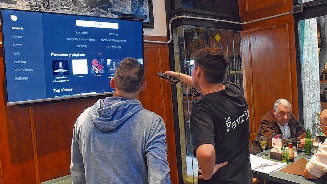 Buscando la conexión. Control en mano el muchacho intenta conectarse a Facebook y ver el encuentro.