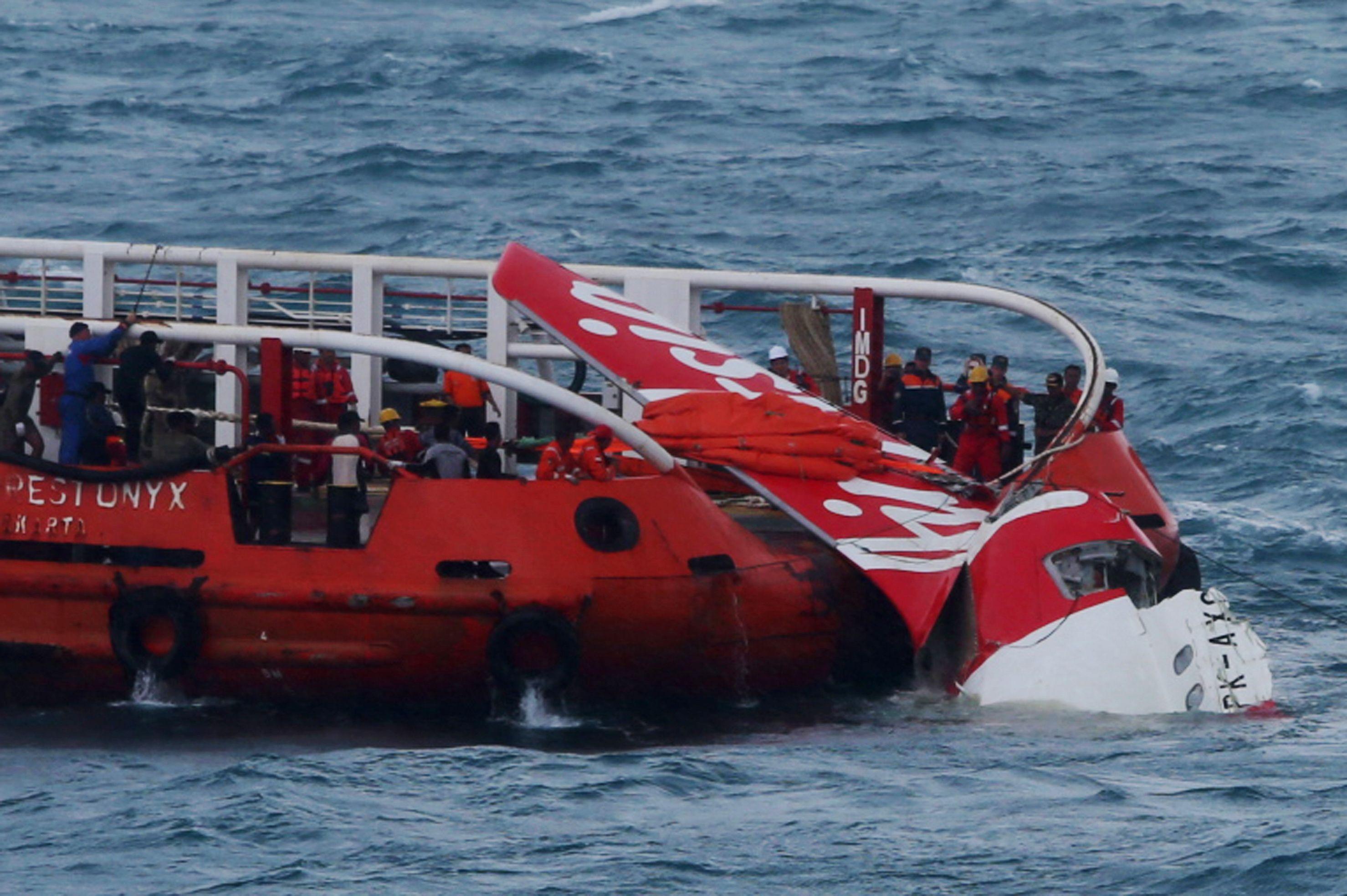 Rescatistas y marinos de Indonesia durante el rescate la cola del avión de Air Asia. (Foto: Reuters)