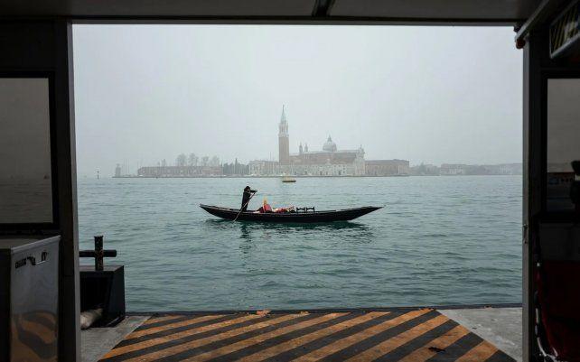 Un gondolero viaja en su barca vacía a través de la cuenca de San Marco con la iglesia de San Giorgio Maggiore, como fondo, en Venecia.