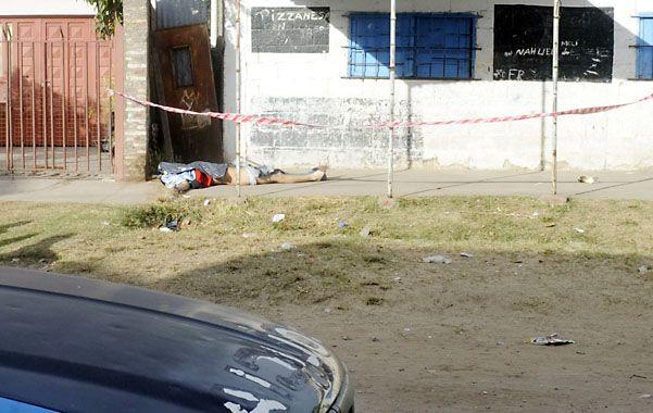 EN LA VEREDA. El cuerpo de Navarro quedó tendido frente a una rotisería.