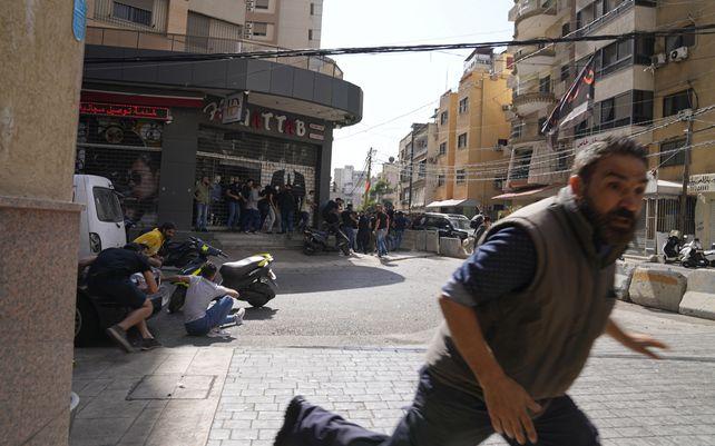 Un hombre corre para refugiarse de los partidarios del grupo chiíta, aliado con armas de fuego de Hezbolá, durante los enfrentamientos armados que estallaron durante una protesta en el suburbio de Dahiyeh, en el sur de Beirut, Líbano, el jueves 14 de octubre de 2021.